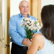 Mature man giving bunch of flowers to woman — Stock Photo