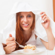 Happy woman eating sweet cake under sheet — Stock Photo #40793997