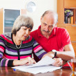 Mature couple reading financial document — Stock Photo
