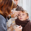 Stock Photo: Parents measuring temperature of unwell boy