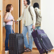 Couple with luggage looking in mirror near door — Foto Stock