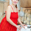 Happy woman in red cleans gas stove with sponge — Stock Photo