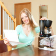 Beautiful woman reading warranty card for new coffee machine — Stock Photo