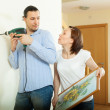 Man and woman hanging picture — Stock Photo