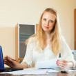 Wistful blonde woman working with financial documents — Stock Photo