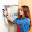 Serious woman turning off the light-switch — Stock Photo