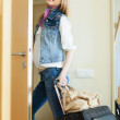 Positive woman with luggage leaving home — Stock Photo #40795693