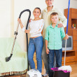 Happy family dusting in home — Stock Photo #40796293