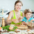 Mother with her daughter making a wonderful fish dumplings — Stock Photo