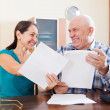 Stock Photo: Happy senior couple holding documents at home