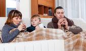 Freezing family of three warming near warm radiator — Stock Photo