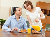 Happy couple having breakfast with croissants — Stock Photo