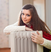 Long-haired woman near oil heater — Stock Photo