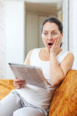 Förvånad mogen kvinna ser ut tidningen — Stockfoto