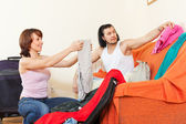 Couple sitting on sofa and packing suitcase — Photo