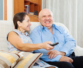 Happy mature couple looking TV — Stock Photo