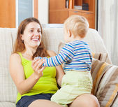 Happy mom with child on sofa — Stock Photo