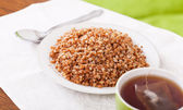 Buckwheat porridge in plate with cup of tea — Stock Photo
