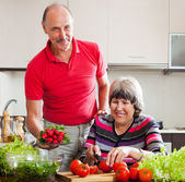 Senior man and mature woman cooking lunch — Stock Photo
