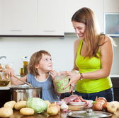Smiling woman with baby cooking — Stock Photo