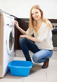 Woman doing laundry with washing machin — Stock Photo