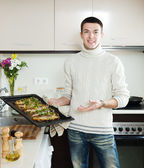 Guy with cooked fish on frying pan — Stock Photo