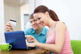 Couple shopping online in living room — Stock Photo