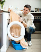 Guy putting clothes in to washing machine — Stock Photo