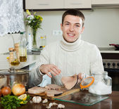 Happy handsome man cooking steak of porbeagle — Stockfoto