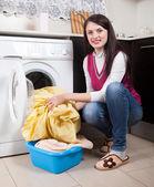 Happy brunette woman doing laundry — Stock Photo