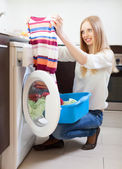 Woman looling clothes near washing machine — Stock Photo