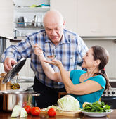 Mature couple cooking food with vegetables — Stock Photo