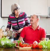 Loving mature couple cooking in kitchen — Stock Photo