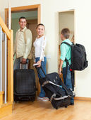 Ordinary family of three with luggage looking in mirror — Stock Photo