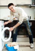 Guy loading clothes into the washing machineading clothes into — Stock Photo
