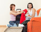 Couple sitting on sofa and packing suitcase at home — Stok fotoğraf