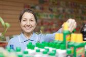 Woman chooses liquid fertilizer at store — Stock Photo