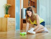 Woman rubbing wooden floor — Stock Photo