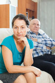 Sad mature woman against husband at home — Stock Photo