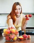 Woman taking peaches at table in home — Stock Photo