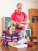 Serious mature couple reading document — Stock Photo