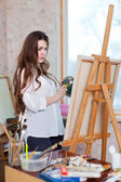 Long-haired woman paints with oil colors — Stock Photo