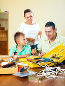 Ordinary nice family of three making something with the working — Stock Photo
