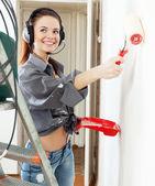 Happy girl in headphones paints wall — Stock Photo