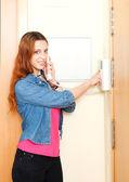 Giovane bella donna dai capelli rossi utilizzando il videocitofono di casa coperta — Foto Stock