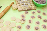 Rolling pin, dough and raw pelmeni — Stock Photo