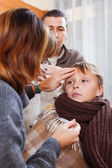 Parents measuring the temperature of unwell boy — Stock Photo