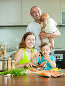 Family of four cooking red fish at home kitchen — Stock Photo