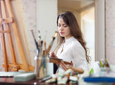 Long-haired woman paints on canvas — Stock Photo