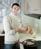 Man putting raw steak of fish into frying pan — Stock Photo